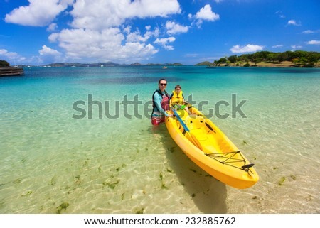 Family of mother and son on colorful yellow kayak at tropical beach during summer vacation