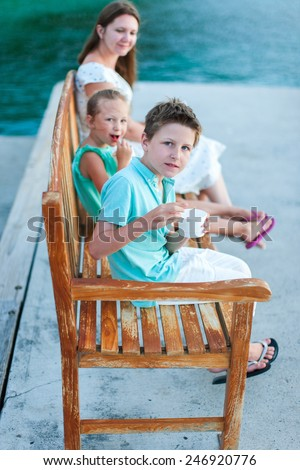 Family of mother and two kids outdoors on summer day - stock photo