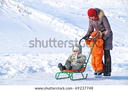Family of mother and two kids teachin skate on the winter rink - stock photo