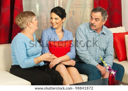 Family of mother,daughter and father having conversation and sitting together on couch in living room - stock photo
