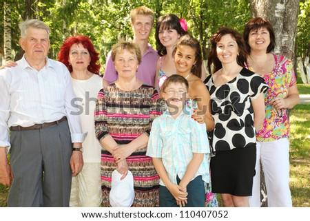 Family of nine people pose at park near big green tree - stock photo