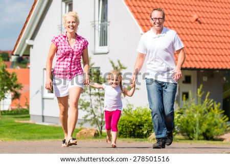 Family of Parents and child walking in front of home in village or suburb - stock photo