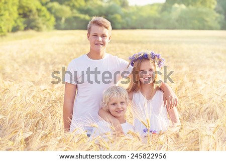 Family of three children, siblings hugging in the wheat summer field. Happy children hugging, concept of relationship and togetherness.  - stock photo