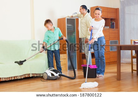 family of three doing housework  in home