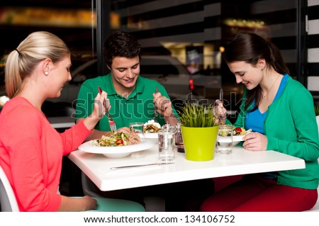 Family of three enjoying meal at restaurant. - stock photo