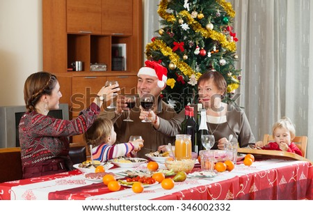 family of three generations celebrating New Year over  table at home