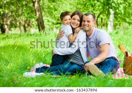 Family of three has picnic in park. Concept of happy family relations and carefree leisure time - stock photo