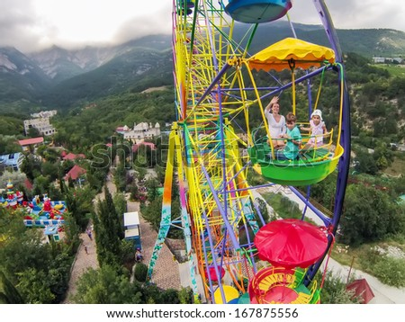 Family of three having fun on the ferris wheel against the mountains and sky with clouds, view from unmanned quadrocopter. - stock photo