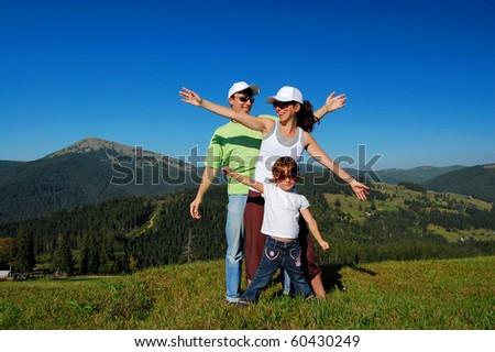 Family of three having fun outdoors - stock photo