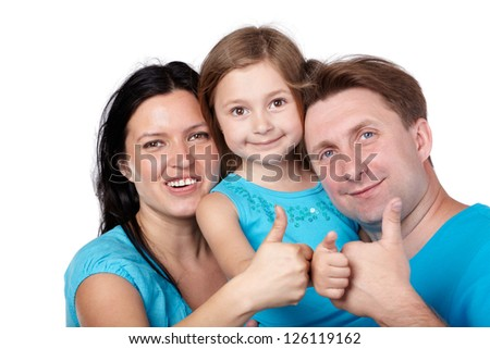 Family of three in blue shirts gives their thumbs up.