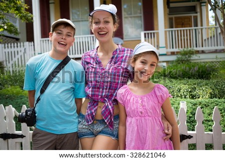 Family of three is standing near the house at summer day. - stock photo