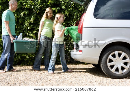 Family of three loading recycling into car, side view - stock photo