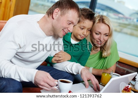 Family of three looking at the laptop screen in cafe - stock photo