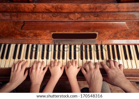 Family of three people is playing the piano, front view. Point of view shot - stock photo