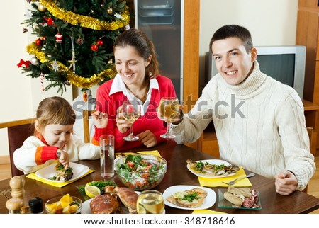 Family of three posing for  Christmas portrait around festive table at home - stock photo