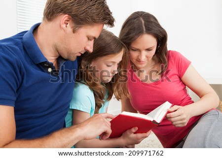 Family of three reading book together at home - stock photo