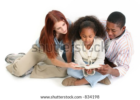 Family of three reading child's bible together.  Caucasian mother and African American Father with daughter. - stock photo