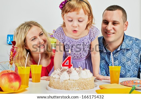 Family of three sits at birthday table, daughter blows out candle on cake and parents look at her - stock photo