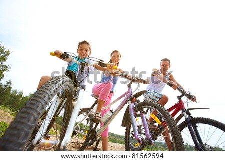 Family of three sitting on bikes, looking at camera and smiling - stock photo