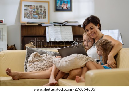 Family of three sitting on the sofa and using laptop together - stock photo