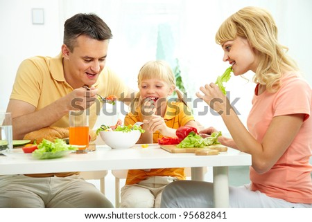 Family of three together at table eating fresh salad