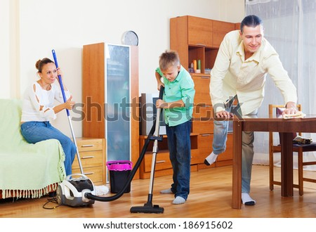 family of three with teenager doing housework together