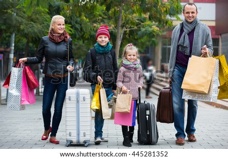 Family of tourists with kids carrying shopping bags outdoors
