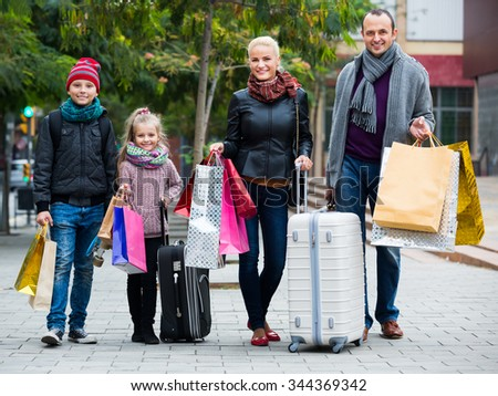 Family of tourists with kids carrying the shopping bags outdoors