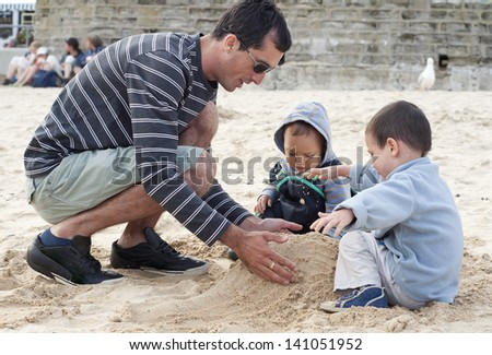 family of two children and father  building sandcastle from sand on a beach on a cold day. - stock photo