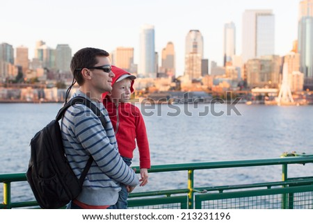 family of two enjoying ferry boat ride in seattle with great city skyline view at sunset - stock photo