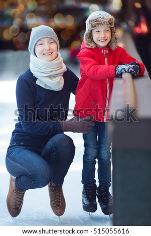 family of two enjoying ice skating at winter at outdoor skating rink decorated for holiday time, winter and family concept