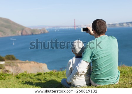 family of two enjoying the view of famous san francisco sightseeing - golden gate bridge and taking picture with phone - stock photo