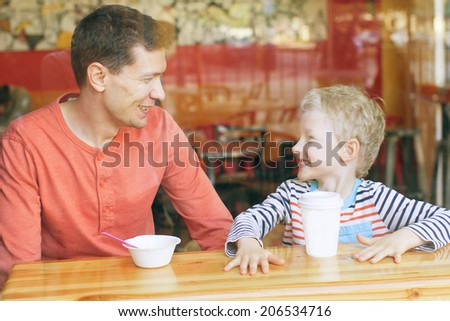 family of two enjoying time together in cafe - stock photo