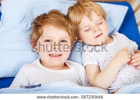 Family of two little brothers: little boys having fun in bed at home, indoors.