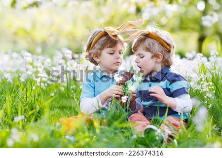 Family of two siblings: Little boys wearing Easter bunny ears at spring green grass and blooming apple garden, eating chocolate bunny and having fun outdoors. On warm sunny day