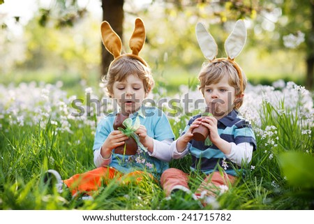 Family of two siblings: Little boys wearing Easter bunny ears at spring green grass and blooming apple garden, eating chocolate bunny and having fun outdoors. - stock photo