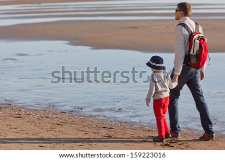 family of two walking by the ocean - stock photo