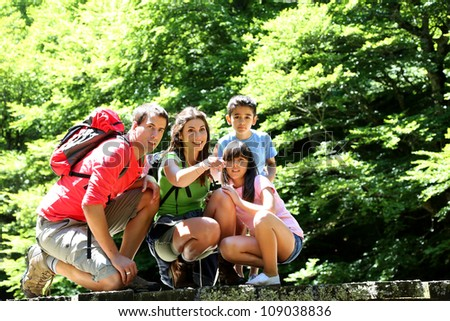 Family on a bridge in mountain observing nature - stock photo