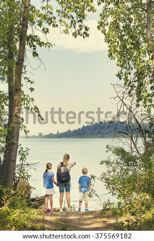 Family on a day hike together near a beautiful mountain lake - stock photo
