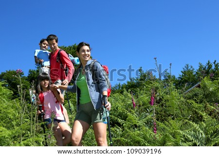 Family on a hiking day going down hill - stock photo