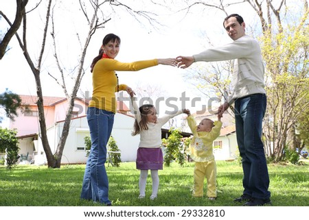 Family on a lawn in front of the house
