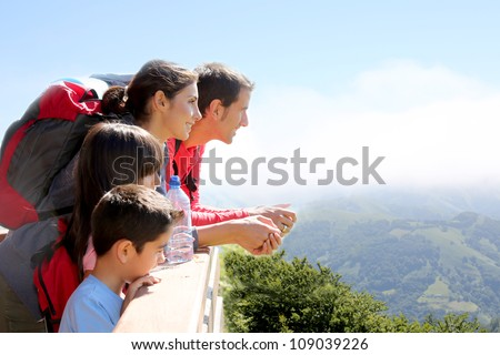 Family on a trek day in the mountain looking at the view - stock photo