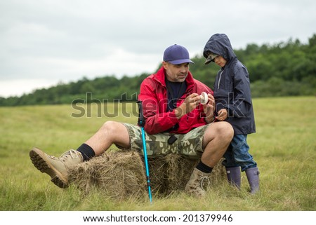Family on a trekking day. Father and son relaxing after a forest and plain trail - stock photo