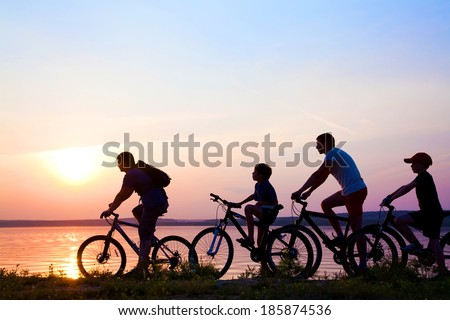 family on bicycles admiring the sunset on the lake. silhouette - stock photo