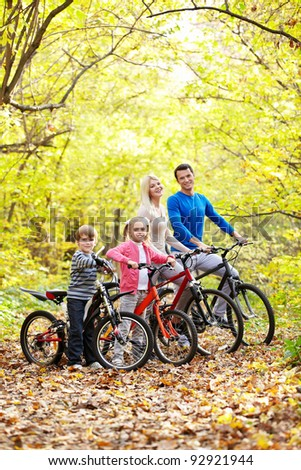 Family on bikes in the park - stock photo