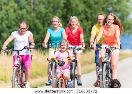 Family on bikes riding down dirt path, mother, father and children together - stock photo
