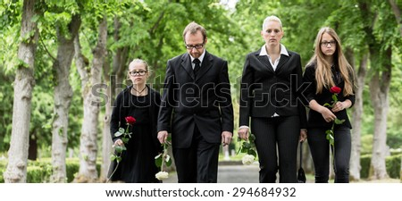 Family on cemetery walking down alley at graveyard with roses - stock photo