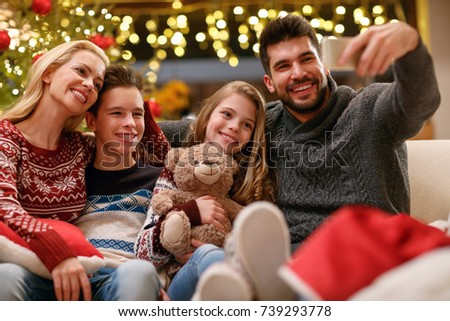 Family On Christmas Holiday Making Selfie Together With Cell Phone