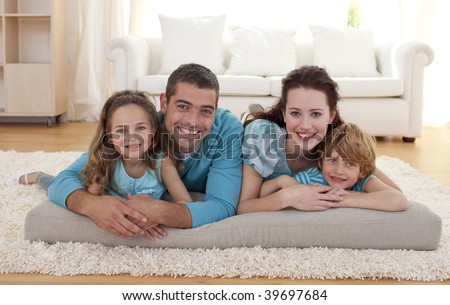 Family on floor lying in living-room - stock photo