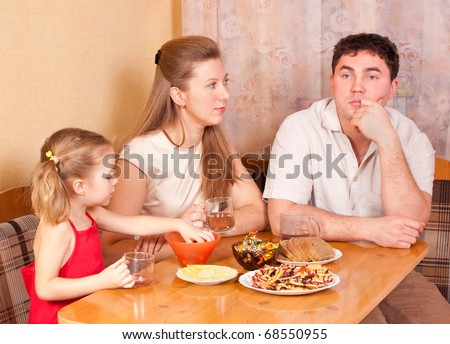 Family on kitchen behind a table, conversation - stock photo